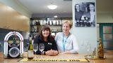 Two female Mercy Health workers stand at a bar bench smiling. A mini jukebox, wine bottle and wine glasses are on top of the bench.