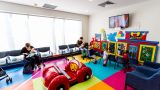 A long shot of a colourful waiting room and childrens playroom. A man and a woman sit while feeding babies, and three young children play with wall mounted activities.