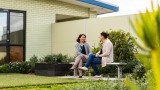Two women sit on a metal park bench in a small garden at Mercy Health talking, one woman is smiling.