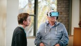 An elderly man in a wheelchair and grey tracksuit wears a virtual reality headset while a male Mercy Health worker kneels nearby,